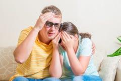 Homme et femme sur le divan observant le film effrayant Photographie stock