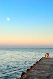 Homme et femme sur un pilier dans le clair de lune Photographie stock libre de droits