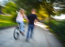 Homme et femme sur une bicyclette passant par l'allée d'automne Photos stock
