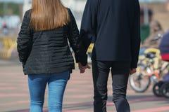 Homme et femme sur une promenade tenant des mains Photo stock