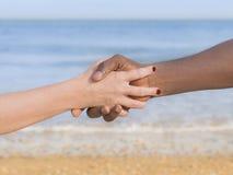 Homme et femme tenant chaque main d'other's (symbole de l'amour et de la diversité) Photographie stock libre de droits