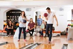 Homme et femme tenant des boules de bowling dans le club Photographie stock libre de droits