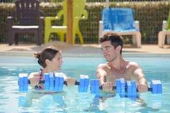 Homme et femme tenant des flotteurs dans la piscine image libre de droits