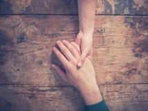 Homme et femme tenant des mains à une table Image libre de droits