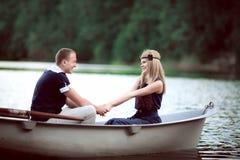 Homme et femme tenant des mains dans le bateau Images libres de droits
