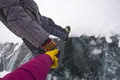 Homme et femme tenant des mains pendant l'hiver sur la glace du lac Baïkal Image libre de droits