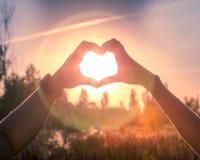 Homme et femme tenant des mains sous forme de coeur dans la perspective du soleil Image libre de droits