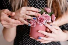 Homme et femme tenant des roses dans la tasse cramoisie Photographie stock