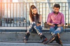 Homme et femme tenant des téléphones Image stock