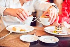 homme et femme tenant la tasse de café, avec des coeurs en café Photographie stock libre de droits