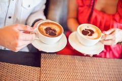 homme et femme tenant la tasse de café, avec des coeurs en café Images stock