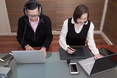 Homme et femme travaillant sur des ordinateurs portables Image stock