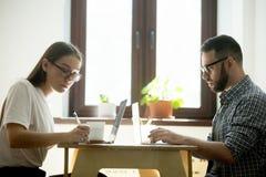 Homme et femme travaillant sur des ordinateurs portables dans un café, faisant des notes Photo libre de droits