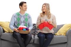 Homme et femme tricotant ensemble sur un sofa Photographie stock libre de droits