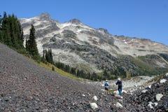 Homme et femme trimardant à la base de la montagne de boucle Images stock