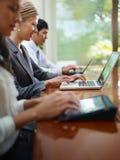 Homme et femmes d'affaires tapant sur le PC au cours du contact Photographie stock