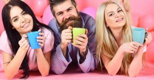 Homme et femmes dans des vêtements domestiques, pyjamas Le plan à trois détendent dans le matin avec du café Amants buvant du caf Images libres de droits