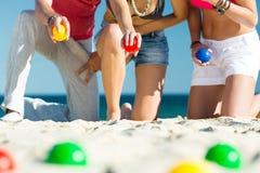 Homme et femmes jouant le boule sur la plage Images stock
