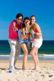 Homme et femmes jouant le boule sur la plage Photo stock