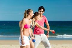Homme et femmes jouant le boule sur la plage Image libre de droits