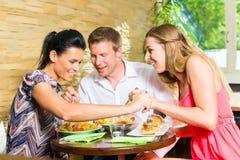 Homme et femmes mangeant de la salade fraîche pour le petit déjeuner Images stock