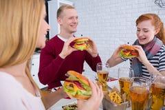 Homme et femmes mangeant des hamburgers Photographie stock