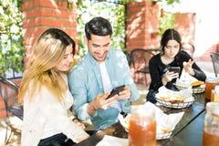 Homme et femmes utilisant des téléphones portables au magasin d'hamburger photographie stock