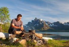 Homme et feu de camp au coucher du soleil Touriste regardant à Photographie stock libre de droits