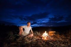 Homme et feu de camp la nuit Photo stock