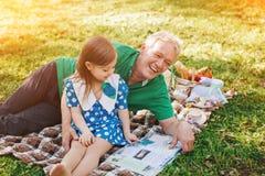 Homme et fille avec le livre sur le plaid Photos stock