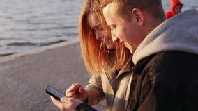 Homme et fille heureux à l'aide du smartphone sur un quai sur le coucher du soleil banque de vidéos