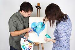 Homme et fille peignant le coeur bleu Photo stock