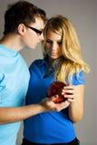 Homme et fille retenant la bille rouge Photographie stock