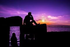 Homme et fille s'asseyant au coucher du soleil Images stock