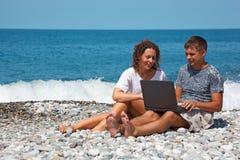 Homme et fille s'asseyant sur le bord de la mer Images stock