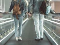 Homme et fille se tenant sur l'escalier mobile Photos stock