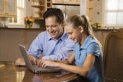 Homme et fille travaillant sur l'ordinateur portatif Photographie stock