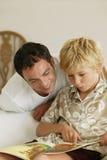 Homme et garçon affichant un livre photographie stock libre de droits