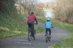 Homme et garçon avec le roulement de bicyclette sur la route en automne photo stock