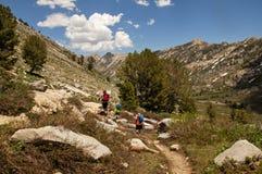 Homme et garçons trimardant dans les montagnes image stock