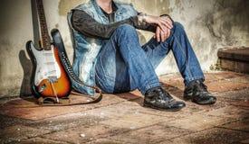 Homme et guitare se penchant contre un mur Images libres de droits