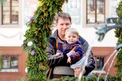 Homme et petit fils près de fontaine avec des oeufs de pâques Photos stock