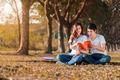 Homme et séance et lecture de femme un livre en parc Image stock