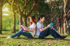 Homme et séance et lecture de femme un livre en parc Images libres de droits