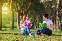Homme et séance et lecture de femme un livre en parc Photographie stock libre de droits