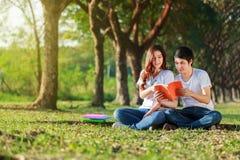 Homme et séance et lecture de femme un livre en parc Images stock