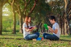 Homme et séance et lecture de femme un livre en parc Photos stock