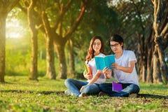 Homme et séance et lecture de femme un livre en parc Photographie stock