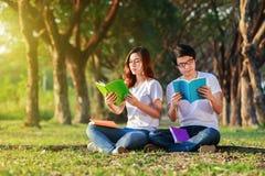 Homme et séance et lecture de femme un livre en parc Photos libres de droits