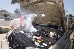 Homme et sien au-dessus du véhicule heated Photo stock